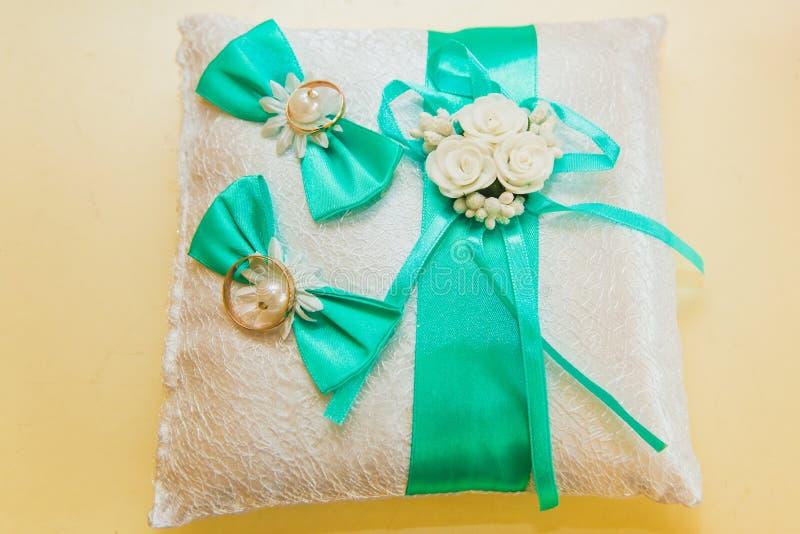 Los anillos de bodas están en una almohada blanca y sadely el ramo de la novia imágenes de archivo libres de regalías