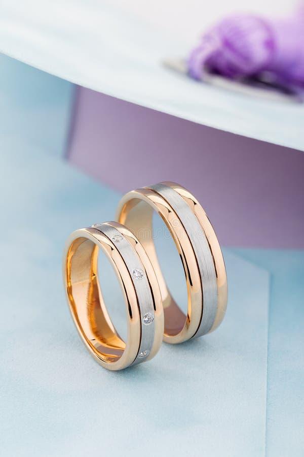 Los anillos de bodas de la plata y del oro congriegan con las piedras preciosas en sobre azul fotografía de archivo libre de regalías