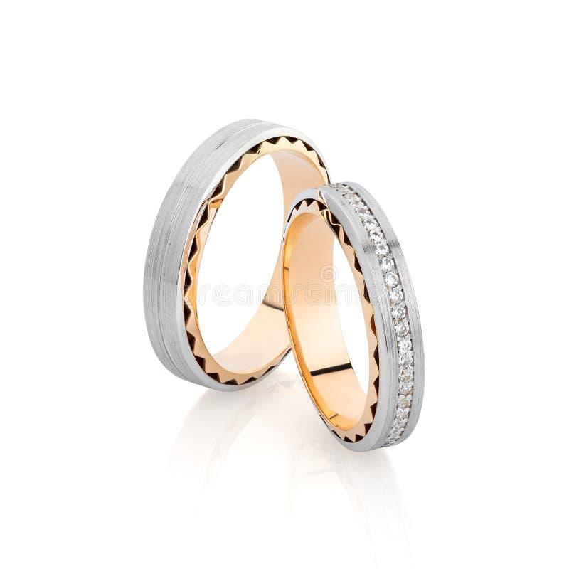 Los anillos de bodas de la plata y del oro congriegan con la superficie y las piedras preciosas del compañero aisladas en blanco fotografía de archivo
