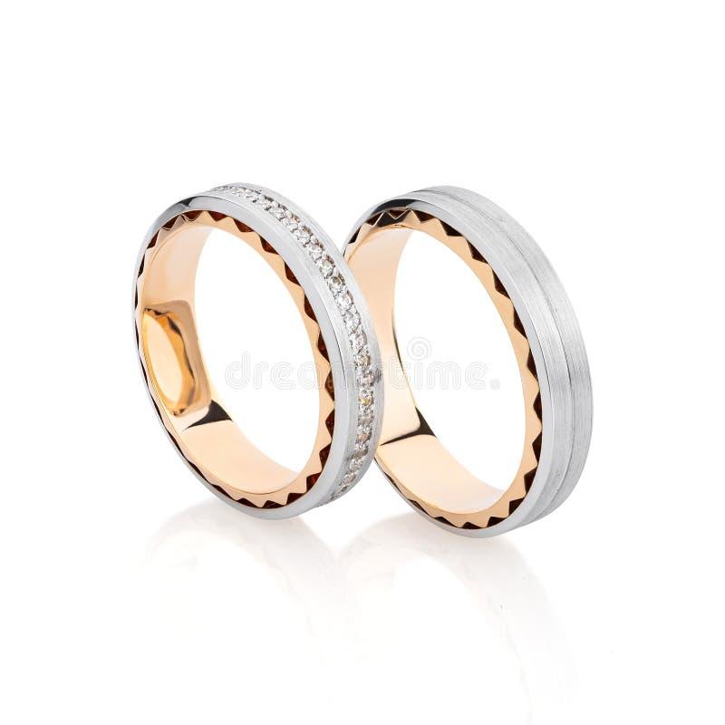 Los anillos de bodas de la plata y del oro congriegan con la superficie y las piedras preciosas del compañero en blanco foto de archivo