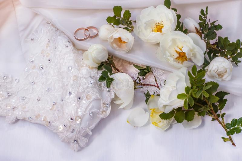Los anillos de bodas de las flores color de rosa salvaje blanco y de oro en la perla blanca colorean la tela foto de archivo