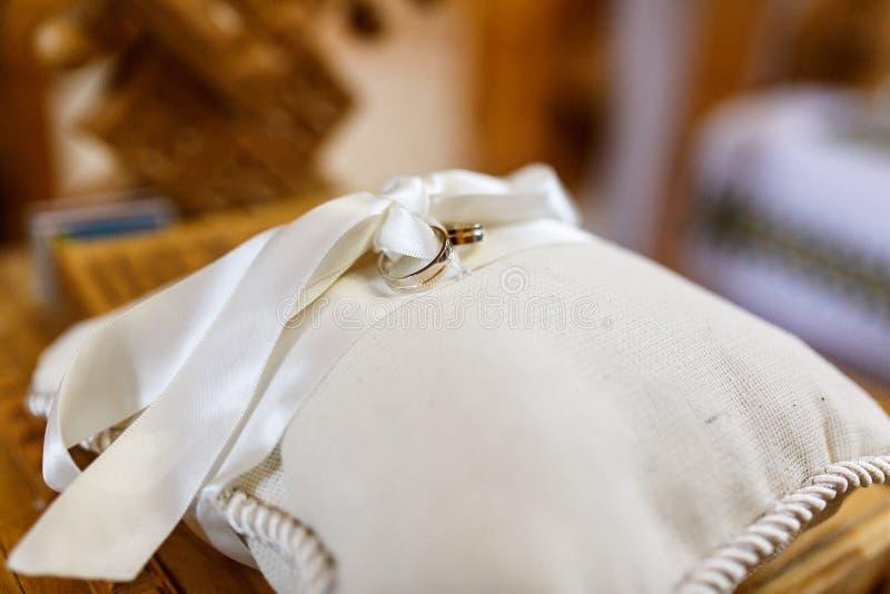 Los anillos de bodas limitaron con la mentira blanca de la cinta en una almohada imagen de archivo