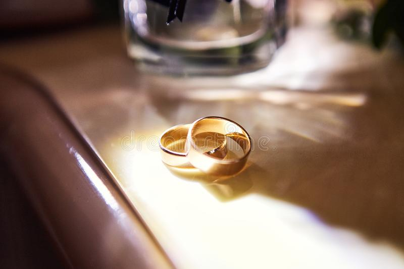 Los anillos de bodas mienten en la tabla cerca de un ramo que se casa fotos de archivo