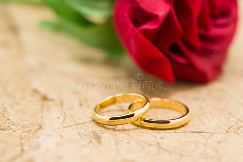 Los anillos de bodas y artificial subieron en fondo marrón fotos de archivo