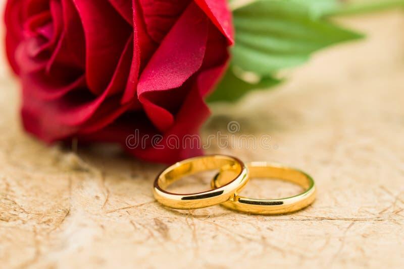 Los anillos de bodas y artificial subieron en fondo marrón imágenes de archivo libres de regalías