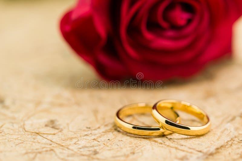 Los anillos de bodas y artificial subieron en fondo marrón foto de archivo libre de regalías