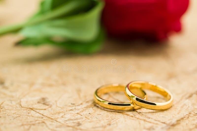 Los anillos de bodas y artificial subieron en fondo marrón fotografía de archivo libre de regalías