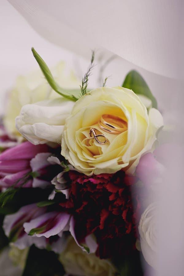 Los anillos de bodas y las flores se cierran para arriba imagen de archivo libre de regalías