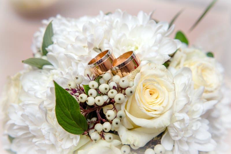Los anillos de compromiso están en el bukete de la boda imagenes de archivo