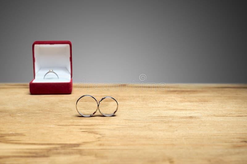 Los anillos de compromiso están en la tabla, y el compromiso posterior fotos de archivo libres de regalías