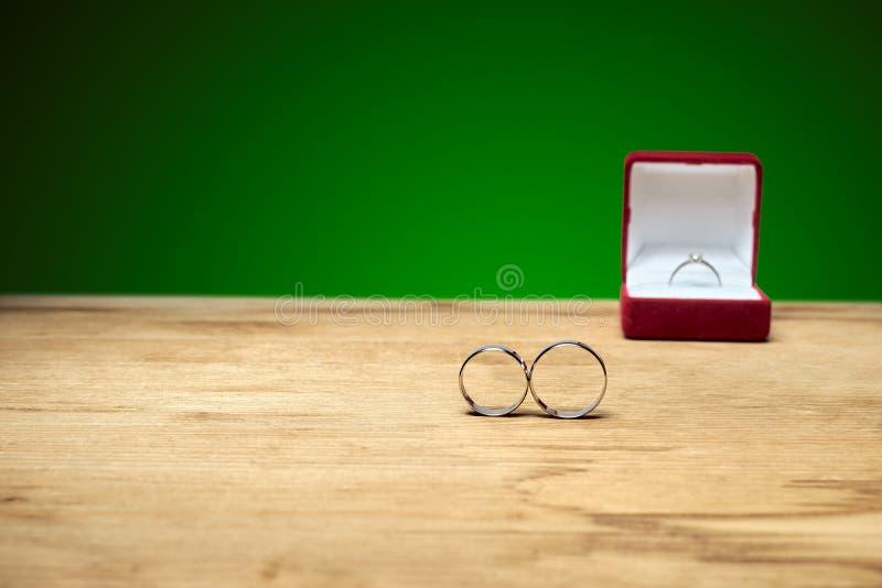 Los anillos de compromiso están en la tabla, y el compromiso posterior fotografía de archivo