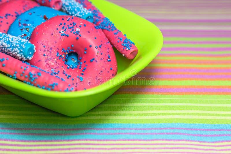 Los anillos de espuma esmaltados con asperjan y los palillos del caramelo en fondo colorido foto de archivo libre de regalías