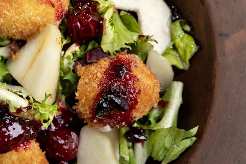 Los anillos de espuma hechos en casa sabrosos del queso atascan, vertido con la pera y salad-2 imágenes de archivo libres de regalías