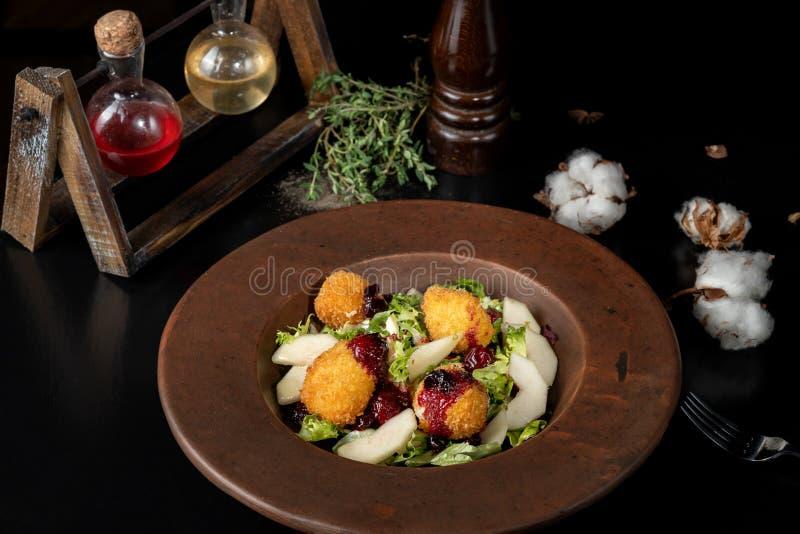 Los anillos de espuma hechos en casa sabrosos del queso atascan, vertido con la pera y salad-2 imagen de archivo