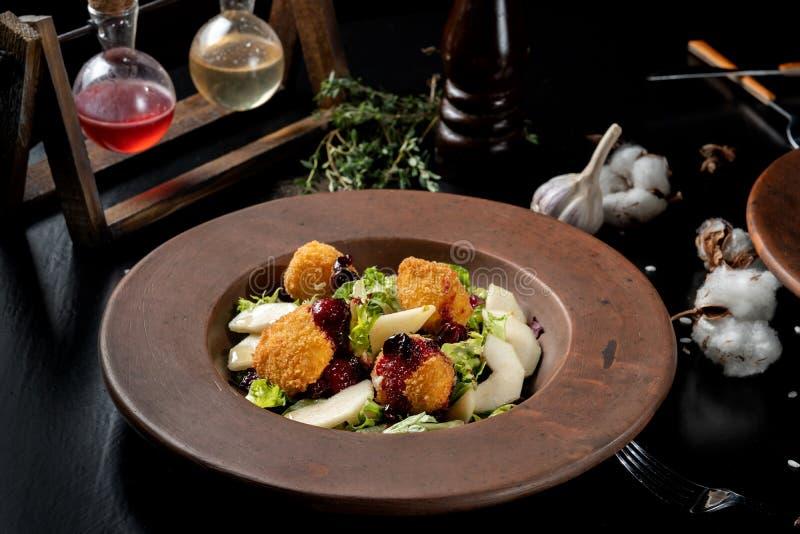 Los anillos de espuma hechos en casa sabrosos del queso atascan, vertido con la pera y salad-3 imagenes de archivo