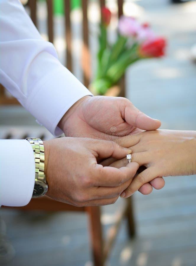 Los anillos del intercambio de los recienes casados, novio ponen el anillo en la mano de la novia imagen de archivo libre de regalías