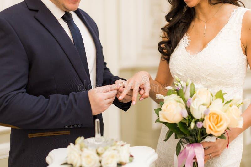 Los anillos del intercambio de los recienes casados, novio ponen el anillo en la mano del ` s de la novia imagenes de archivo