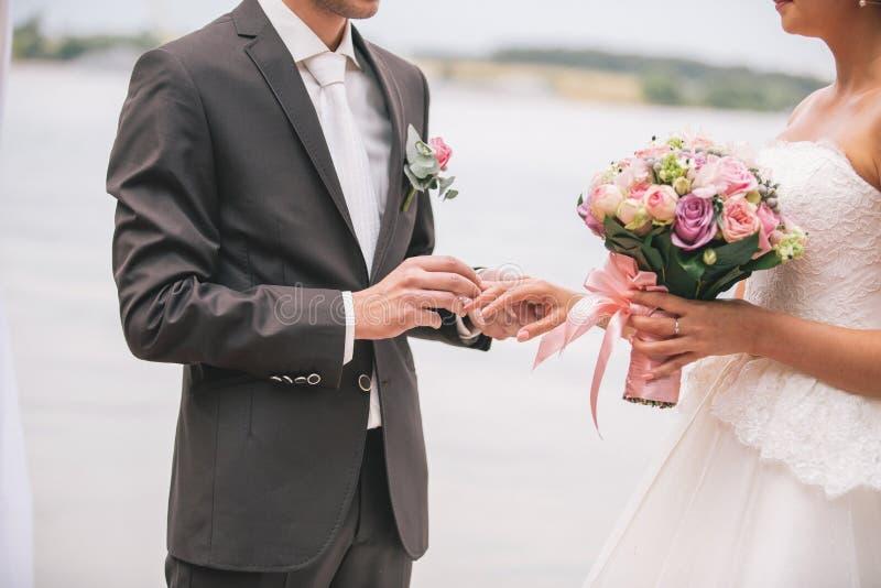 Los anillos del intercambio de los recienes casados, novio ponen el anillo en la mano del ` s de la novia imagen de archivo