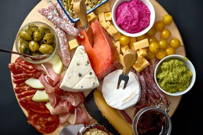 Los Antipasti suben con diversos bocados del queso y de la carne con hummus y aceitunas en el tablero de madera fotos de archivo