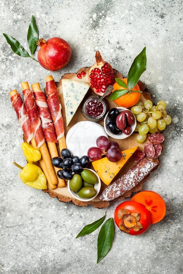 Los aperitivos presentan con bocados de los antipasti La variedad del queso y de la carne sube sobre fondo concreto gris Visión s fotografía de archivo libre de regalías