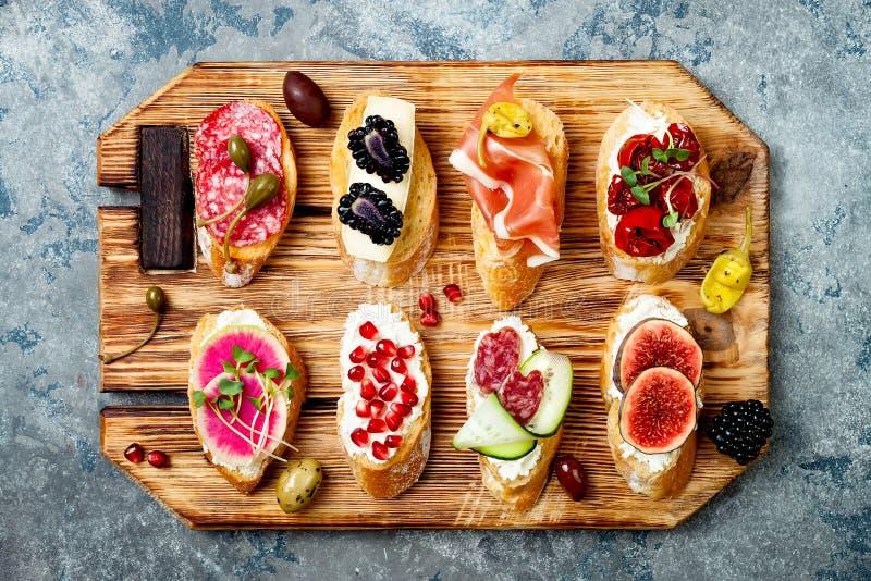 Los aperitivos presentan con bocados italianos de los antipasti Brushetta o tapas españoles tradicionales auténticos fijados fotos de archivo libres de regalías