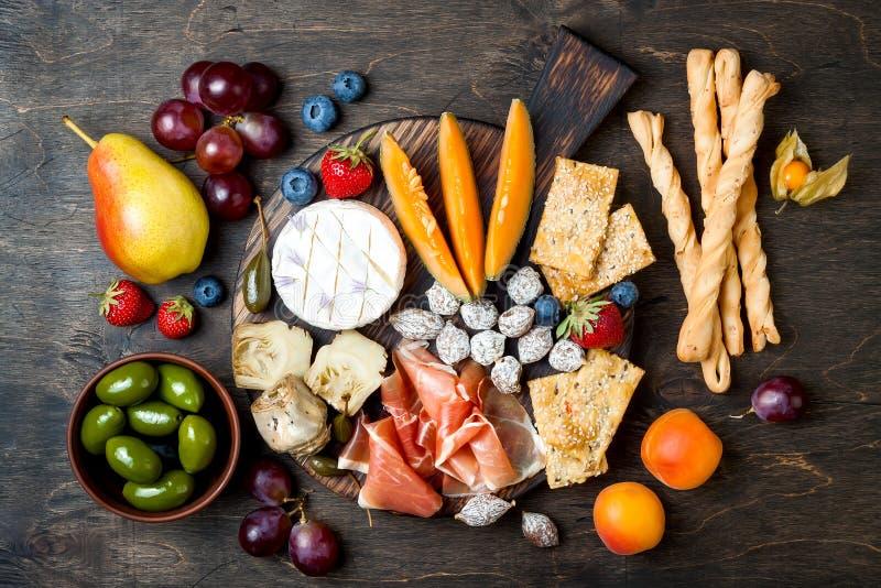 Los aperitivos presentan con bocados italianos de los antipasti La variedad del queso y del charcuterie sube sobre fondo de mader imagen de archivo libre de regalías
