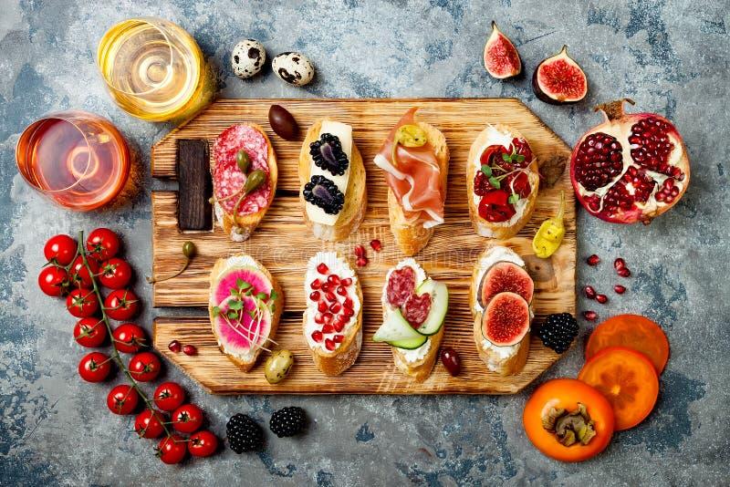 Los aperitivos presentan con bocados y vino italianos de los antipasti en vidrios Brushetta o tapas españoles tradicionales autén imágenes de archivo libres de regalías