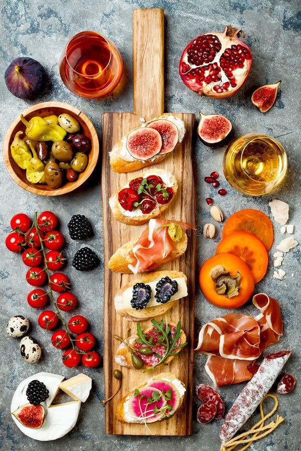 Los aperitivos presentan con bocados y vino italianos de los antipasti en vidrios Brushetta o tapas españoles tradicionales autén imagenes de archivo