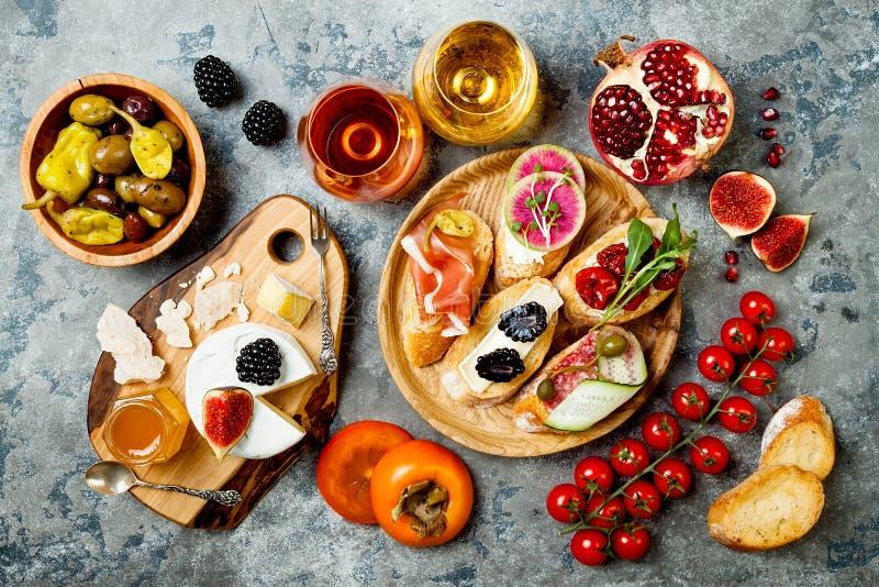 Los aperitivos presentan con bocados y vino italianos de los antipasti en vidrios Brushetta o tapas españoles tradicionales autén foto de archivo libre de regalías