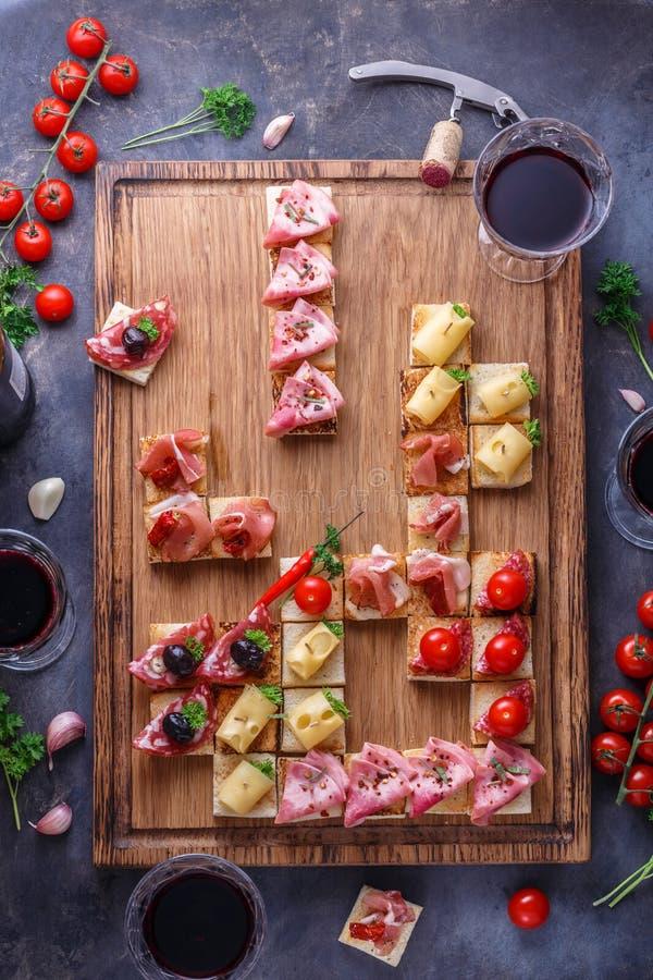 Los aperitivos presentan con bocados y vino italianos de los antipasti en vidrios Brushetta o los tapas españoles tradicionales a foto de archivo libre de regalías