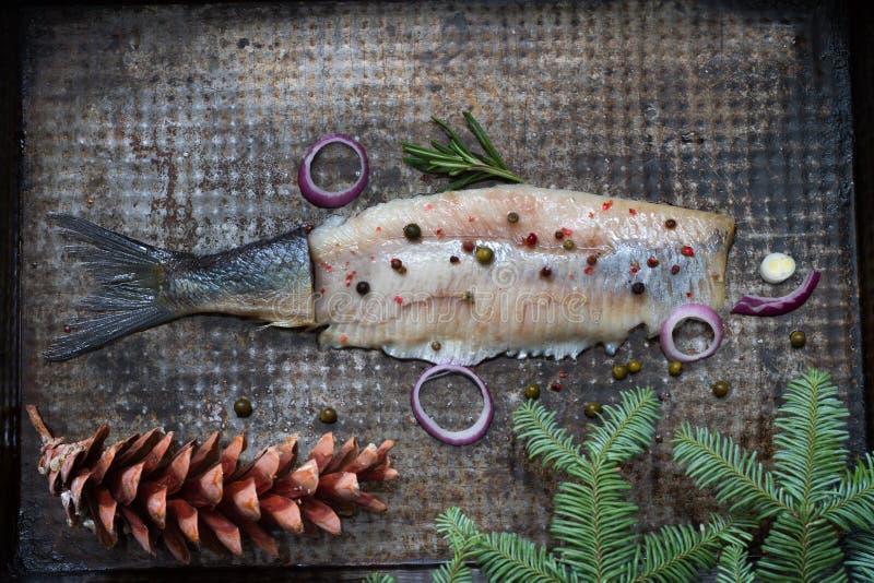 Los arenques abstractos pescan con las especias y el ornamento de la Navidad en vida inmóvil creativa plateada de metal imagen de archivo libre de regalías