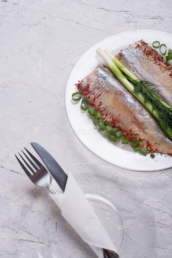 Los arenques adobados cortan en una placa transporant con la cebolla verde y los condimentos servido en estilo escandinavo El coc foto de archivo
