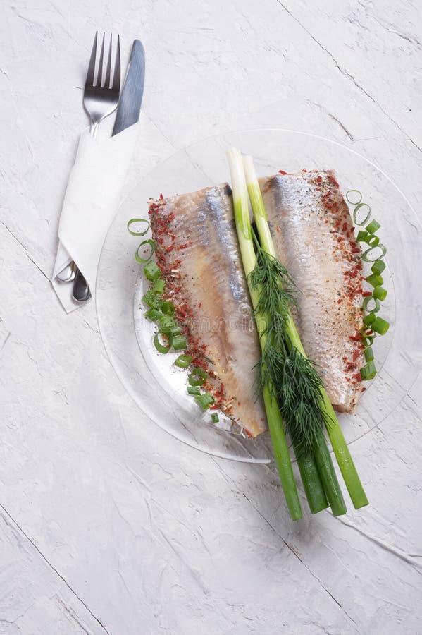 Los arenques adobados cortan en una placa transporant con la cebolla verde y los condimentos servido en estilo escandinavo El coc fotografía de archivo