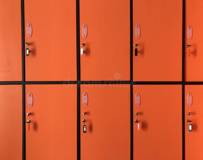 Los armarios anaranjados en gimnasio tienen muchas puertas cerradas con llaves imagen de archivo