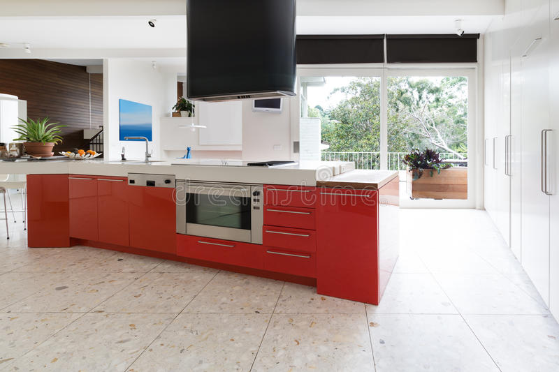 Los armarios de cocina del rojo anaranjado en la isla bench en Aus de lujo moderno fotografía de archivo libre de regalías