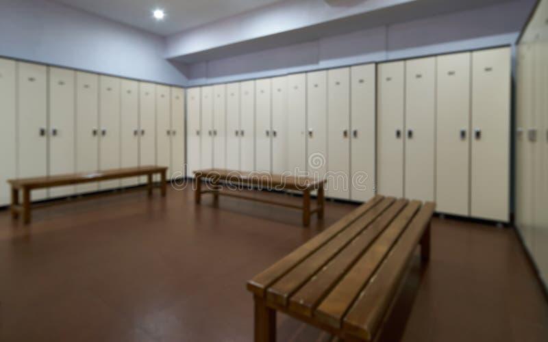 Los armarios grandes con un banco de madera en un vestuario con las puertas se cerraron fotos de archivo