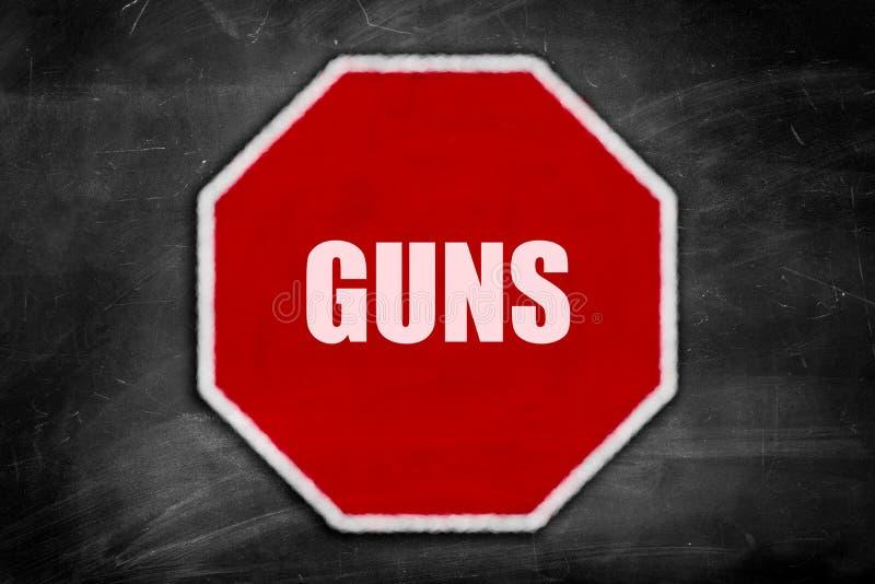 Los armas escritos en una parada firman en una pizarra negra imagenes de archivo