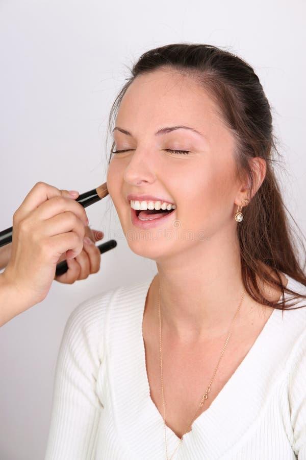 Los artistas de maquillaje aplican el modelo del maquillaje foto de archivo