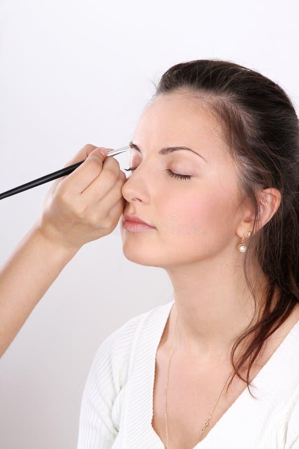 Los artistas de maquillaje aplican el modelo del maquillaje imagen de archivo