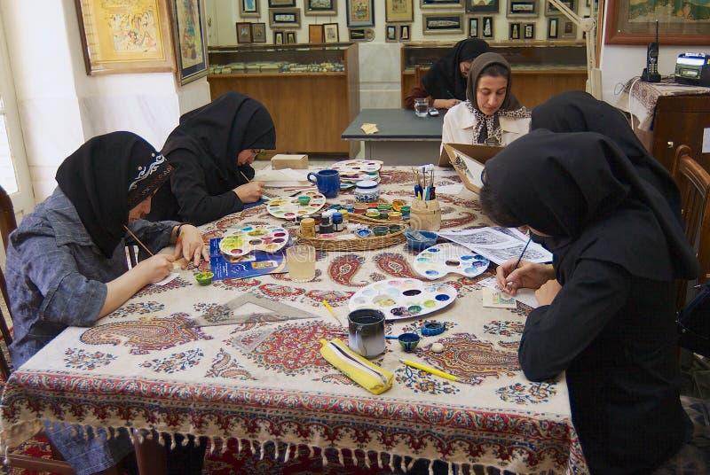 Los artistas musulmanes de las mujeres en headscarfs negros pintan la miniatura persa tradicional en un taller en Isfahán, Irán foto de archivo libre de regalías