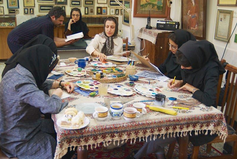 Los artistas musulmanes de las mujeres en headscarfs negros pintan la miniatura persa tradicional en un taller en Isfahán, Irán imagen de archivo