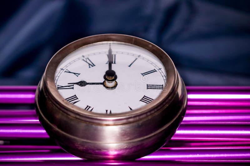 Los Arty tiraron de un reloj grande del reloj de bolsillo del metal en los tubos púrpuras fotografía de archivo libre de regalías