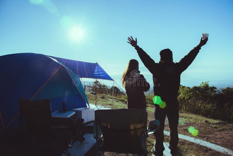 Los asi?ticos de la mujer y del hombre del amante viajan para relajar acampar en el d?a de fiesta En la monta?a mire la subida de foto de archivo libre de regalías