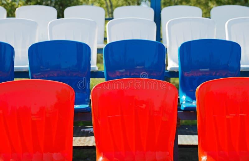 Los asientos rojos y azules del estadio se cierran para arriba fotografía de archivo libre de regalías