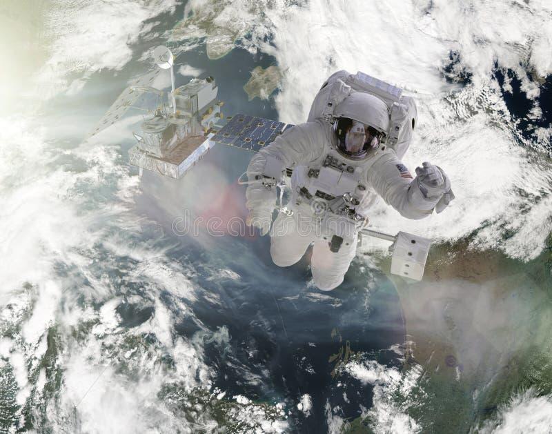 Los astronautas trabajan en los elementos por satélite de esta imagen equipados por la NASA fotos de archivo