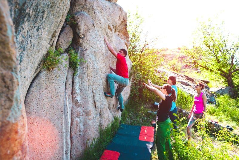 Los atletas bouldering al aire libre imagen de archivo