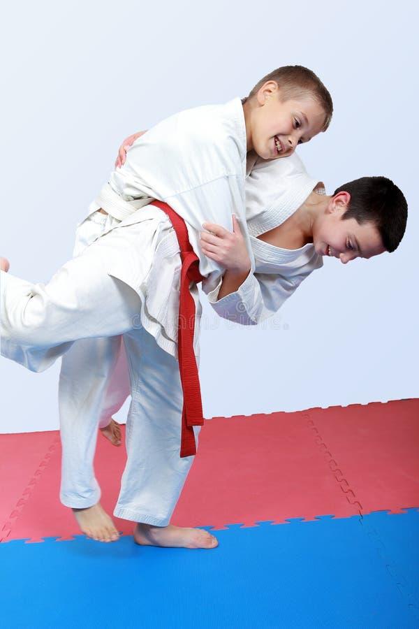 Los atletas con un marco blanco y rojo hacen el tiro de judo fotos de archivo
