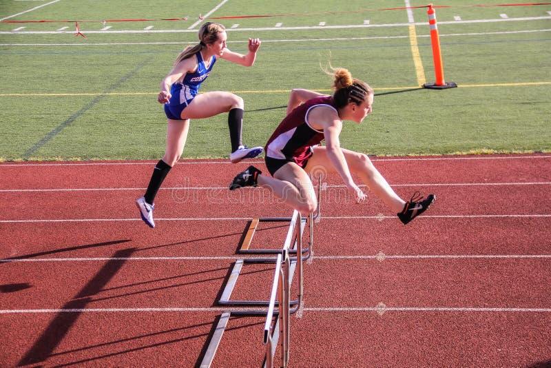 Los atletas de pista de sexo femenino de la High School secundaria despejan obstáculos en carrera de vallas de 300 metros imagen de archivo libre de regalías