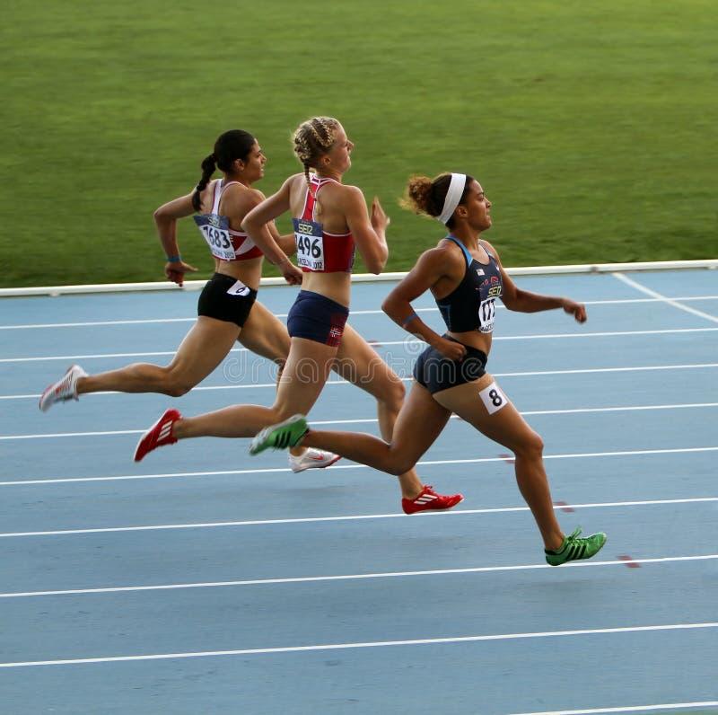 Los atletas en el final de 400 contadores compiten con fotografía de archivo libre de regalías