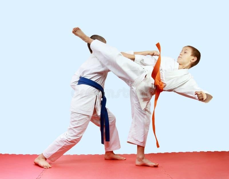 Los atletas jovenes están entrenando a las piernas y a los brazos de los soplos en las esteras imagen de archivo